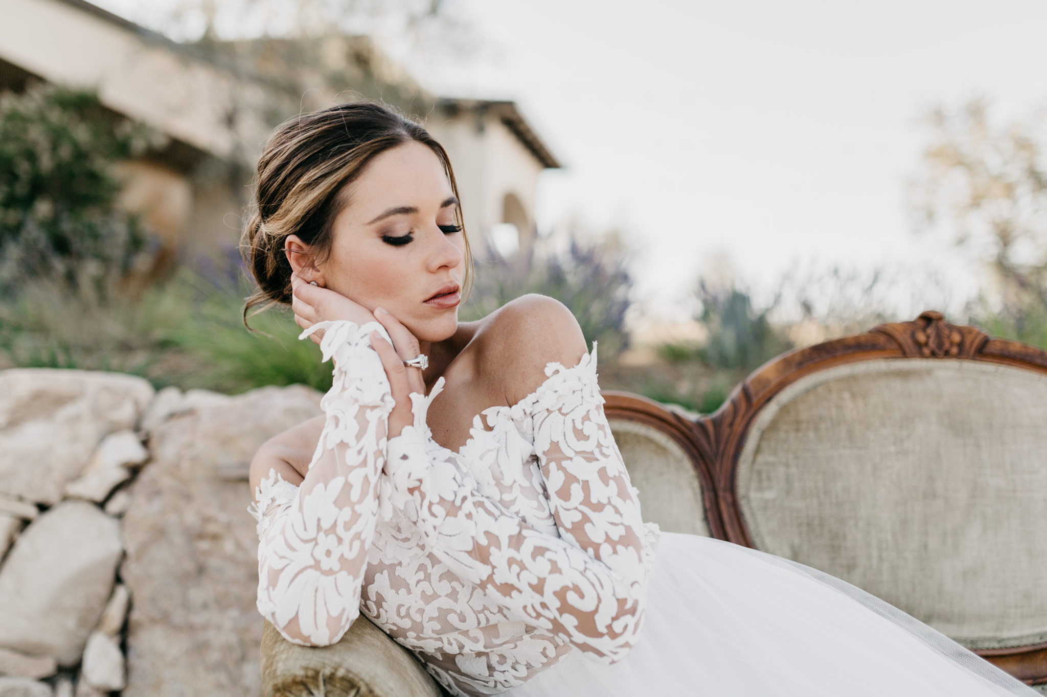 Bride sitting on vintage couch with her eyes closed showing off her makeup
