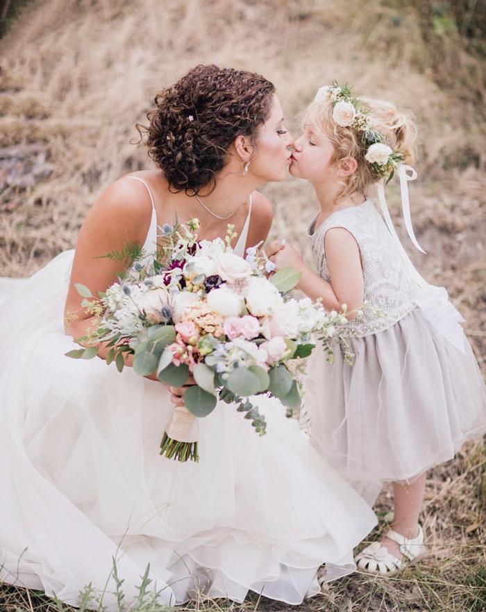 Bride kissing flower girl